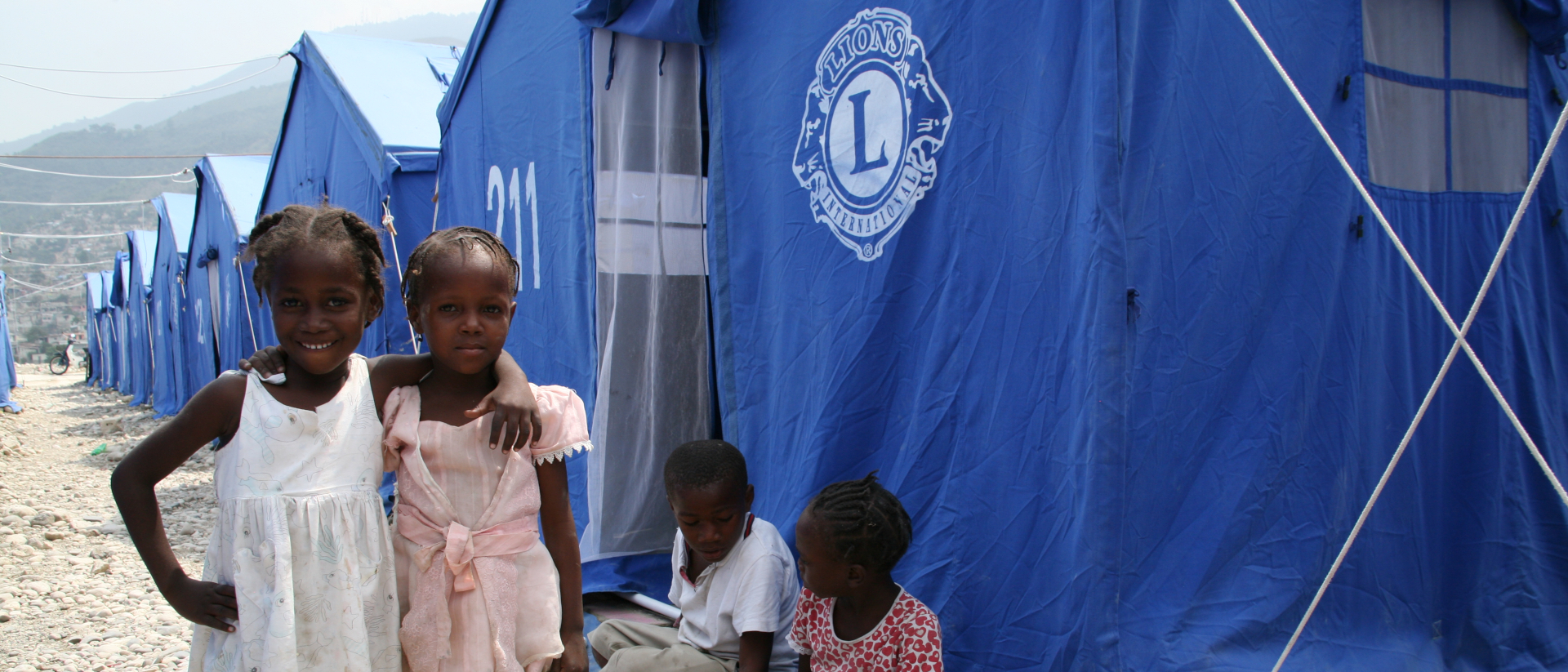 Mädchen stehen vor einer provisorischen Zeltlandschaft